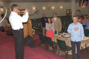 El trompetista nicaragüense, Enrique Leiva, tocó el Himno Nacional de los Estados Unidos de América. Prestan atención, Fernando Cabral. El Pastor y Alcalde Luigi Boria, su esposa Graciela y Eduardo Key.