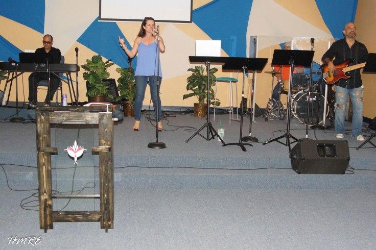 La salmista Elle Zamudio interpretando canciones de alabanza y adoración antes de iniciar la pastora Dania Hernández la primera prédica en Cantares Iglesia.