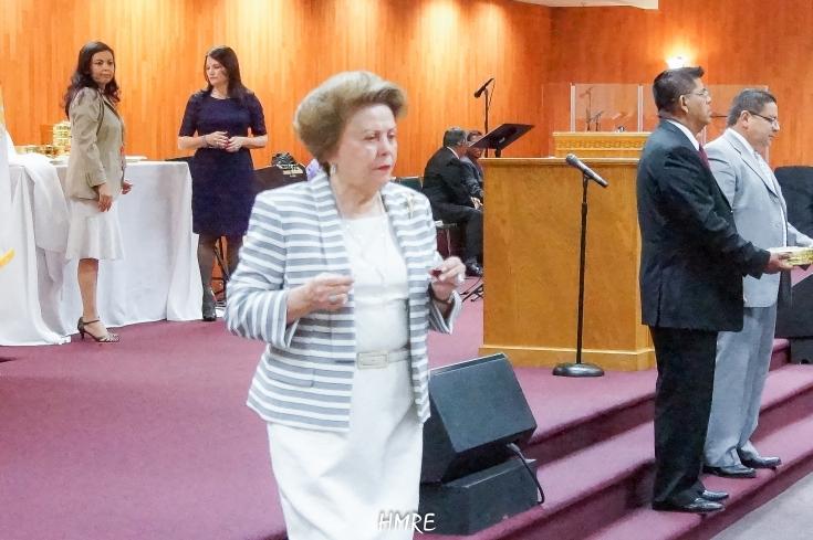 Apóstol Lidia Rodríguez lleva la Comunión a una dama.
